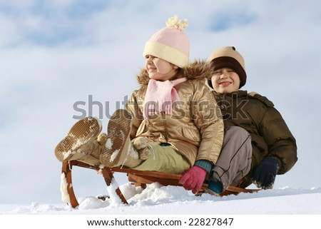 sister and brother on sledge, winter friendship - stock photo