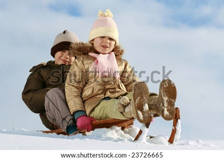 sister and brother on sledge, winter friendship