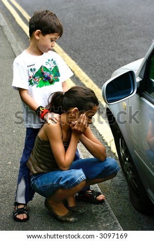 Sister and brother sadly awaits for help by the car after a tyre blew up. - stock photo