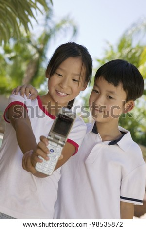 Sister and Brother Using Camera Phone - stock photo