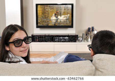 Sister and brother watching 3d film on TV - a series of WATCHING TV images. - stock photo