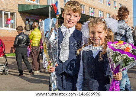 Sister and brother with the flowers on the first day of school - stock photo
