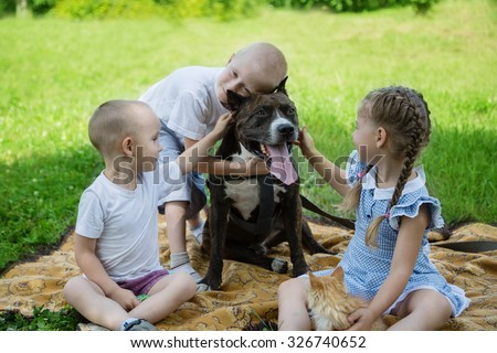 Sister and brothers playing with American Staffordshire Terrier on a lawn.