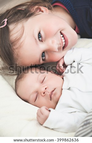 Sister and her newborn brother - stock photo