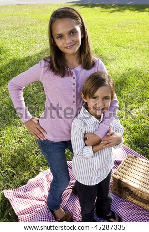Sister and little brother standing on picnic blanket in park - stock photo