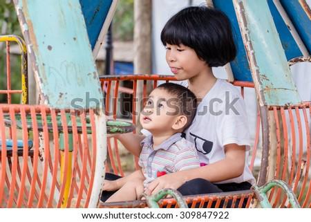 Sister, brother sitting playground. - stock photo