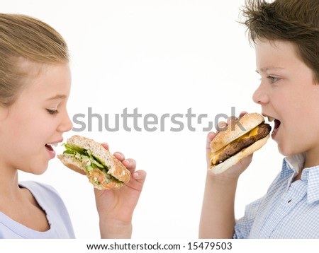 Sister eating sandwich by brother eating cheeseburger - stock photo