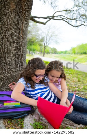 sister friends girls relaxed under tree park after school with bag and folders - stock photo