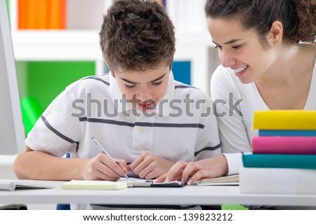 Sister helping brother to writing  homework - stock photo
