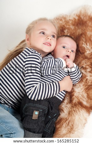 Sister hugging his younger brother - stock photo