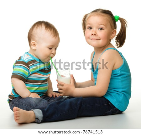 Sister is feeding her little brother and he drinks milk using drinking straw, isolated over white - stock photo