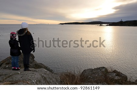 Sisters enjoy a winter coast's sunset