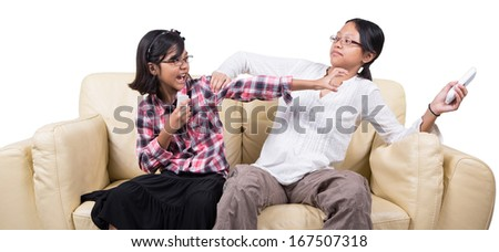 Sisters fighting over remote controls  on a sofa