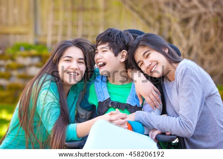 Sisters laughing and hugging disabled little nine year old  brother in wheelchair outdoors - stock photo