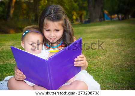 Sisters learning a book outdoor