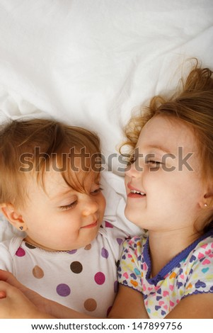 Sisters playing in bed