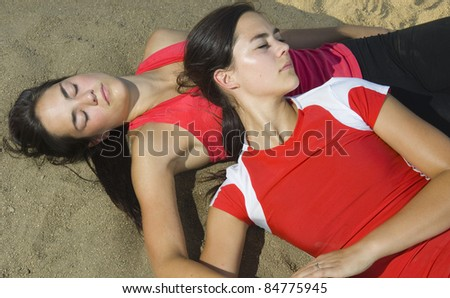 Sisters Relaxing on Beach Volleyball court in summer - stock photo