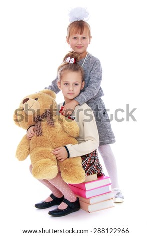 Sisters schoolgirl sitting on a stack of books , hugging a big Teddy bear-isolated on white background - stock photo