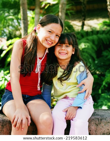 Sisters smiling and hugging - stock photo