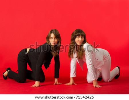 sisters twins in black and white costumes posing in studio