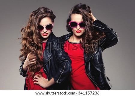 Sisters twins in hipster sun glasses laughing Two fashion models Women smiling positive Friends group having fun, talking Youthful friendship youth adults people culture concept Young women rock party
