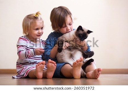 sisters  with cat sitting on the floor indoor - stock photo