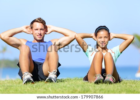 Sit ups - fitness couple exercising sit up outside in grass in summer. Fit happy people working out cross training. Beautiful young multiracial couple, Asian woman, Caucasian man. - stock photo