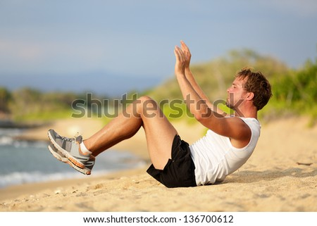 Sit ups - fitness crossfit man doing situps on beach training and working out with high impact. Fit male fitness model in intense workout session on beach outside. - stock photo