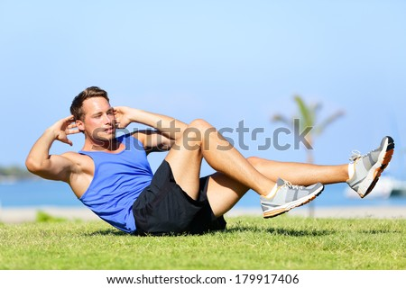 Sit ups - fitness man exercising sit up outside in grass in summer. Fit male athlete working out cross training in summer. Caucasian muscular sports model in his 20s. - stock photo