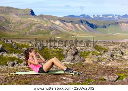 Sit-ups fitness woman doing situps training core outside in amazing nature landscape on Iceland. Fit female sport model girl training crossfit outdoors. Mixed race Asian Caucasian athlete. - stock photo