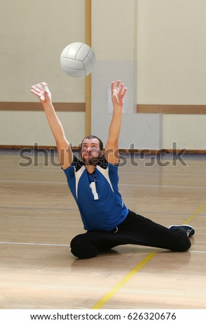Sit volleyball player, legless Paralympic athlete hitting the ball