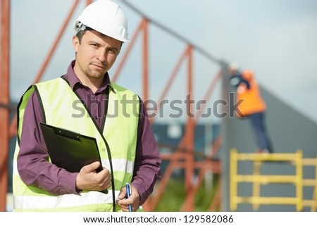 site manager builder worker in uniform and safety protective equipment at construction site in front of metal construction frames - stock photo
