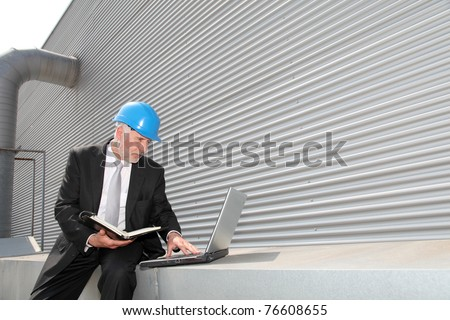 Site manager checking planning on computer - stock photo