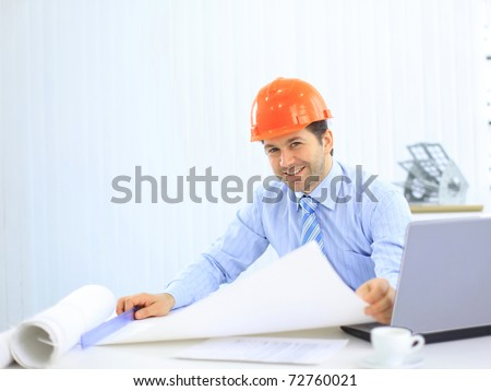 Site manager in the office with blue helmet - stock photo