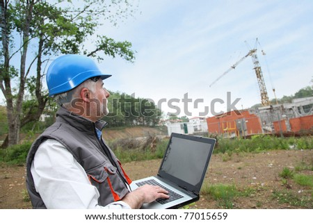 Site manager with laptop computer checking construction - stock photo