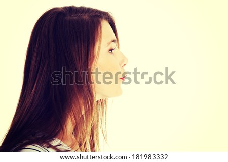 Site view face closeup portrait of a young beautiful caucasian teen sending a kiss