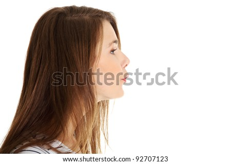 Site view face closeup portrait of a young beautiful caucasian teen sending a kiss, on white. - stock photo
