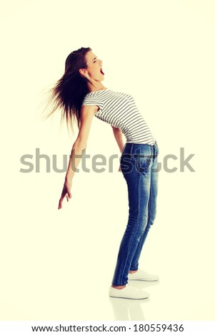 Site view full lenght portrait of a young shouting caucasian teen bending under the wind, on white. - stock photo