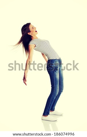 Site view full lenght portrait of a young smiling caucasian teen bending under the wind - stock photo