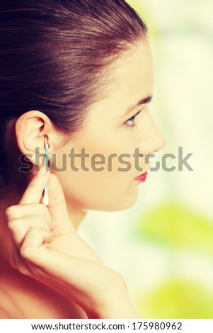 Site view of a face closeup while cleaning up an ear with a swab. - stock photo