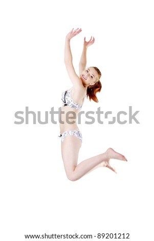 Site view of a smiling young girl jumping and having her hands up, isolated on white background. - stock photo