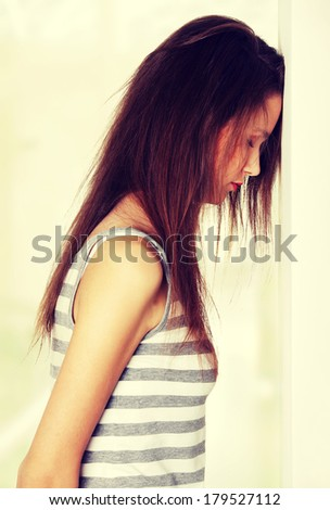 Site view of a young female teen being depressed, resting her head on a wall, on white. - stock photo