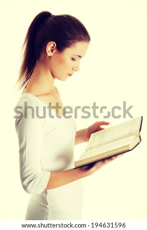 Site view portrait of a beautiful young caucasian teen reading a Bible. - stock photo