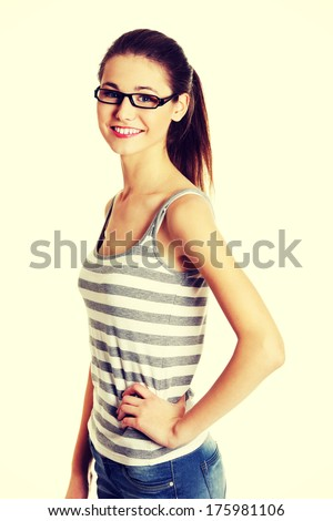Site view portrait of a young female caucasian teen with glasses on her face smiling to the camera, on white. - stock photo