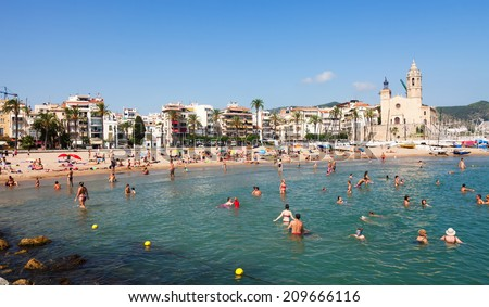 SITGES, SPAIN - AUGUST 6: Mediterranean beach in summer sunny day in August 6, 2013 in Sitges, Spain.  Town is known for its sandy  coast
