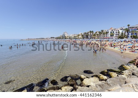 Sitges, Spain - June 7, 2015: Tourists enjoying the beaches of Sitges internationally known, bathed by the Mediterranean Sea - stock photo