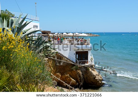 SITGES, SPAIN - MAY 23: The tourists enjoiying their vacation in outdoor restaurant on May 23, 2015 in Sitges, Spain. Up to 60 mln tourists is expected to visit Spain in year 2015. - stock photo