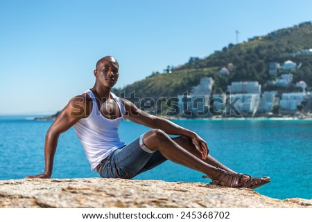 Sitting African black man wearing white vest and blue short jeans. Male model thinking while isolated alone by a blue ocean and sky background. Cape Town South Africa - stock photo