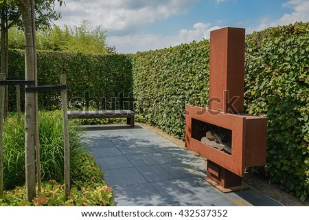 Sitting Area In The Garden With A Fireplace And A Bench Near A Hedge.