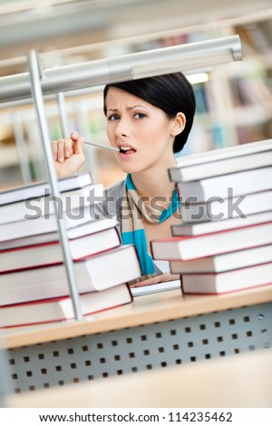 Sitting at the desk student surrounded with piles of books are in panic. Learning process
